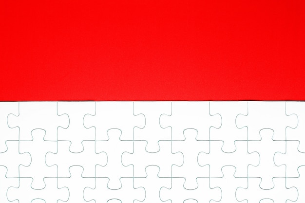 White puzzle pieces on a red background separated