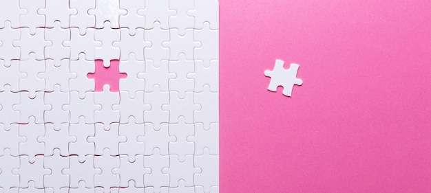 White puzzle on pink background. missing piece.