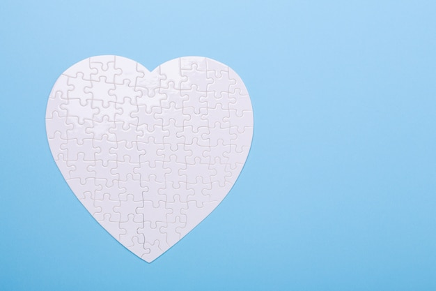 White puzzle in shape of heart on blue