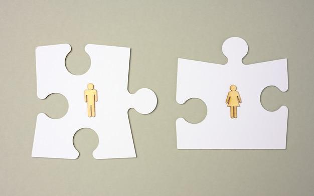 灰色の背景に白いパズルと木製の男性。採用コンセプト、チームの互換性、個性。家族のカップルの互換性