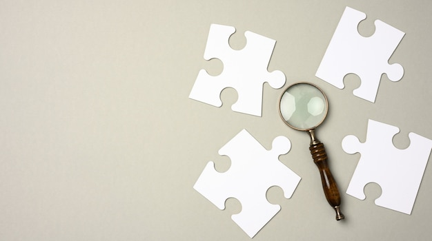 White puzzles around a magnifying glass on a gray background. concept of searching for talented people, recruiting personnel, identifying those capable of career advancement