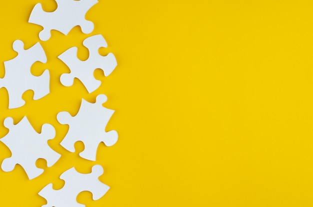White puzzles composition on yellow background. flat lay