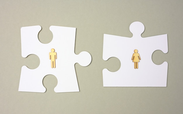 White puzzles and wooden men on a gray background. recruitment concept, team compatibility, individuality. couple compatibility in the family