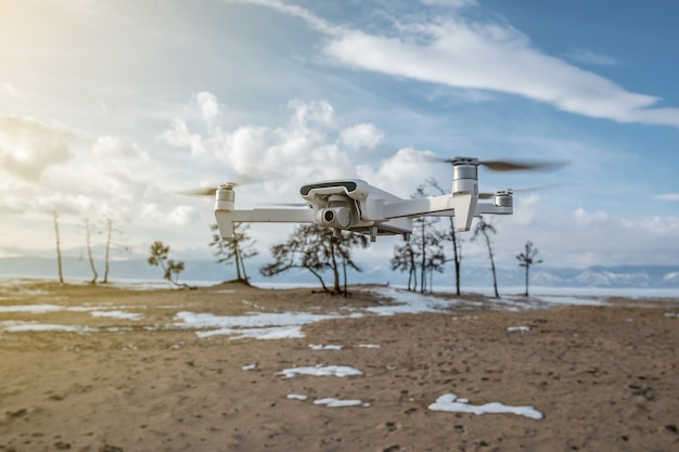 White quadrocopter drone with camera hangs in the air on the background of beautiful nature in winter