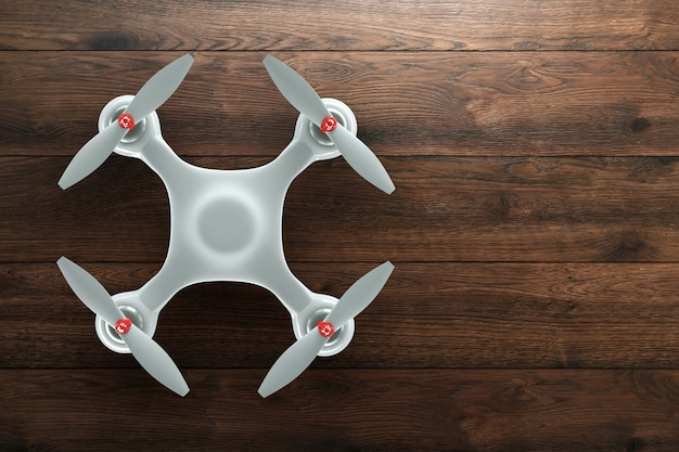 White quadrocopter on wooden brown background with copy space