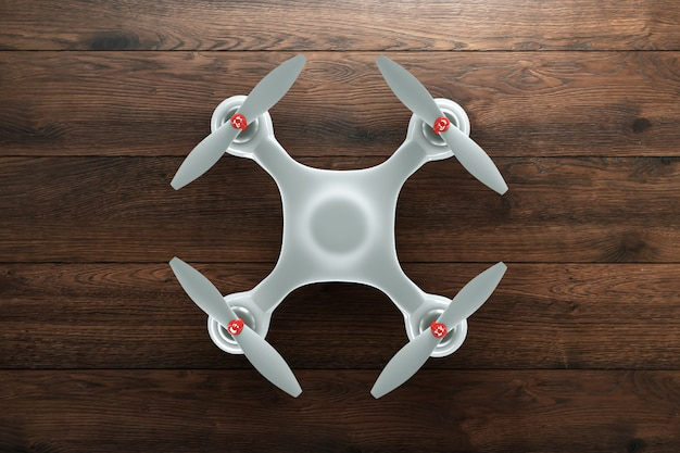 White quadrocopter on wooden brown background