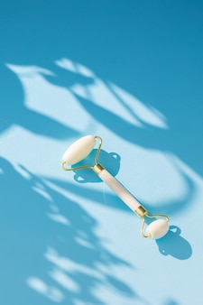 White quartz massager on a womans hand on a blue background massager to tighten the skin on the face