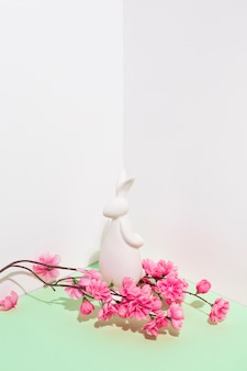White rabbit figurine with flowers branch on table
