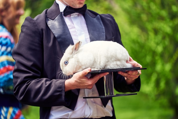 A white rabbit lies on a stand in the magician's hands