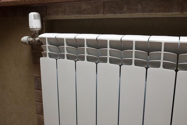 Белый радиатор в ванной комнате крупным планом. обогрев. серая стена, выложенная плиткой.