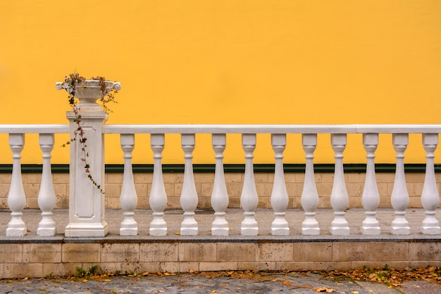 White railing with columns and a vase for flowers. the wall is painted with yellow paint.