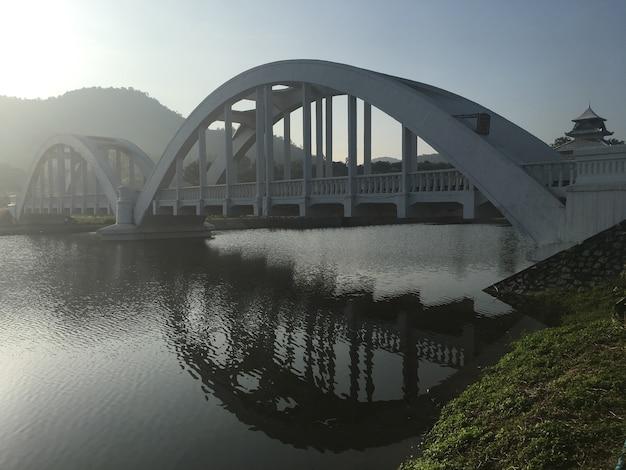 White railway bridge over the lake in the morning sunrise