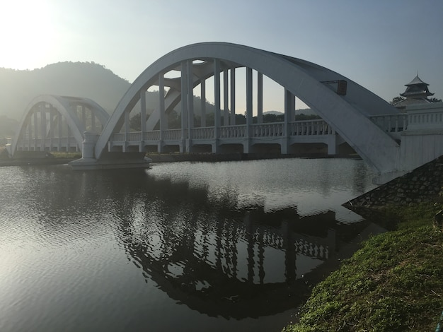 Белый железнодорожный мост через озеро в утренний восход солнца