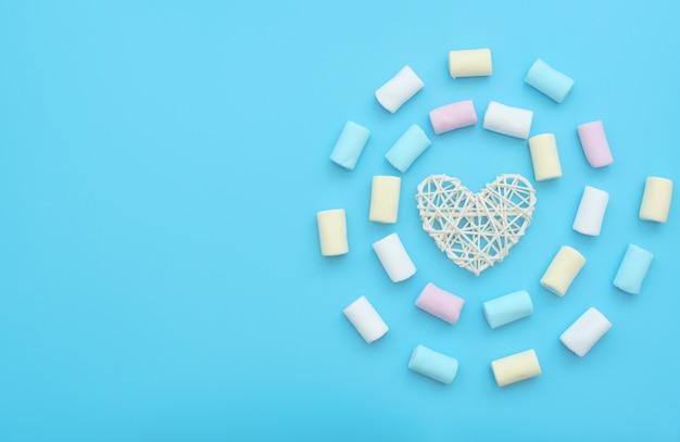 Сердце из белого ротанга и вкусный зефир на синем фоне