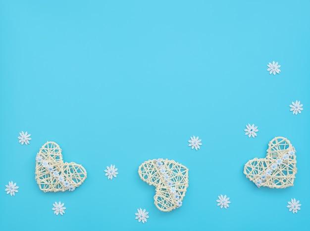 Белые сердца из ротанга с лентой с цветами на синем с кружевными цветами.