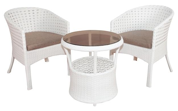 두 개의 의자와 유리 상판이있는 테이블로 구성된 흰색 등나무 고리 버들 가구 세트. 세련된 야외 또는 정원 가구.