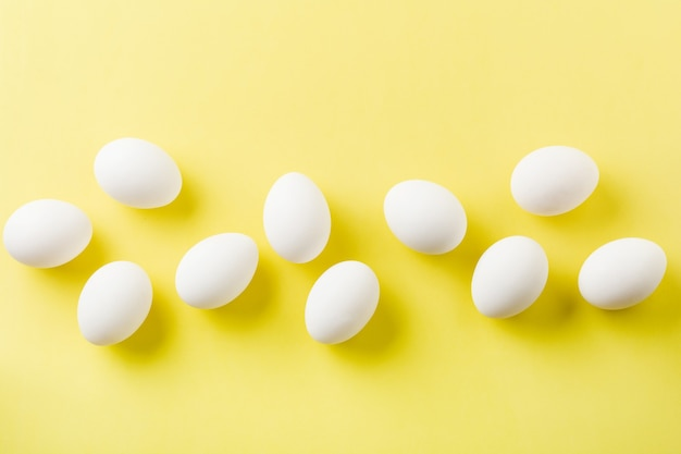 White raw chicken eggs lying in horizontal row with broken egg on yellow surface