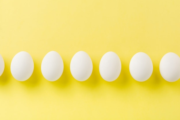 White raw chicken eggs lying on light concrete surface
