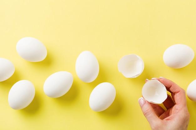 White raw chicken eggs lying on yellow light background and female hand holds broken egg.