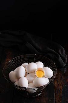 White raw chicken eggs in an old vintage basket on dark surface