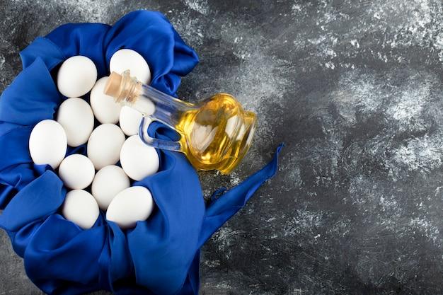 Белые сырые куриные яйца со стеклянной бутылкой масла.