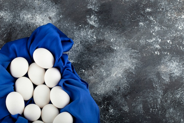 White raw chicken eggs with on a blue tablecloth .