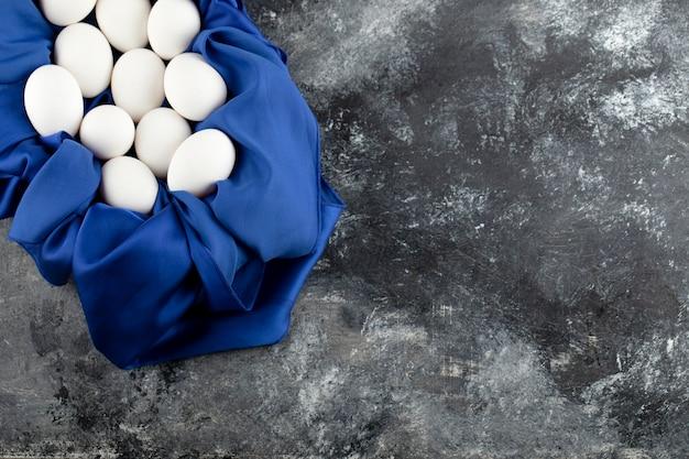 Uova di gallina crude bianche con su una tovaglia blu.