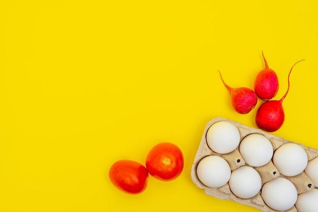 トマト、大根の横にある黄色の背景の側面図の段ボール箱に白い生卵。