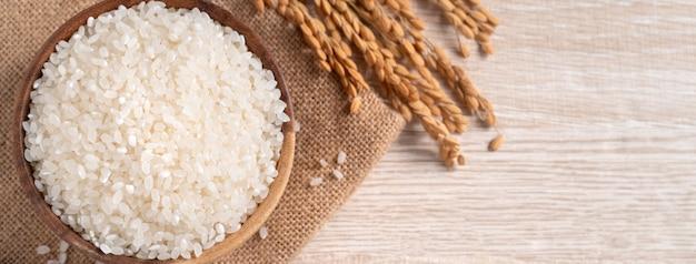 나무 테이블 배경에 귀가 있는 그릇에 흰 생 쌀.