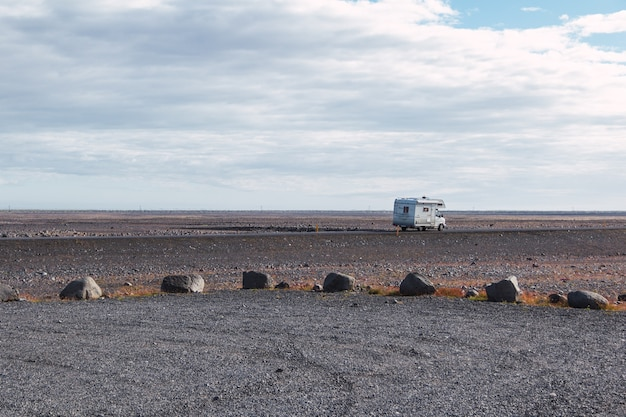 White recreational vehicle on an empty road in iceland