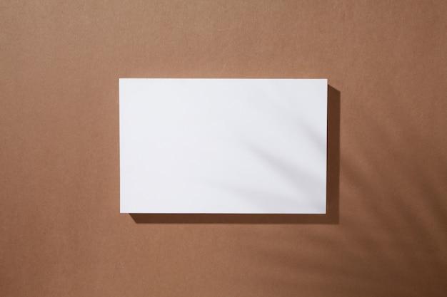 ヤシの葉の影と茶色の背景に白い長方形の表彰台。フラットレイ、上面図。