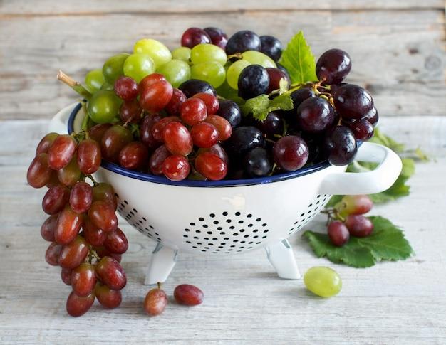 木製のテーブルの上のボウルに白、赤、青のブドウ