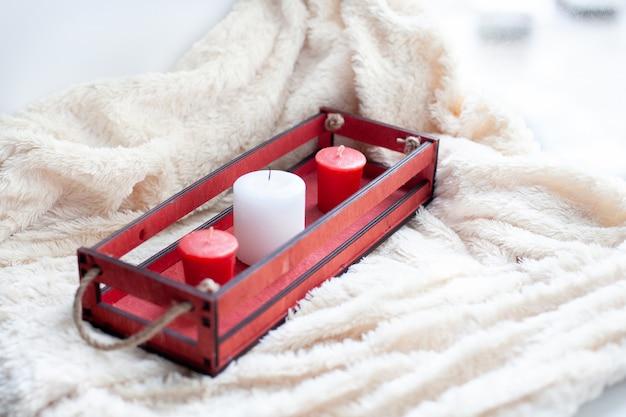 白、赤のキャンドル、ベージュの毛布に赤い木箱。