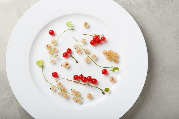 White and red currant berries in a ceramic plate on the table