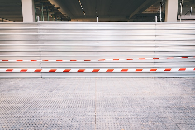 White and red plastic security tapes prevent access to a construction site