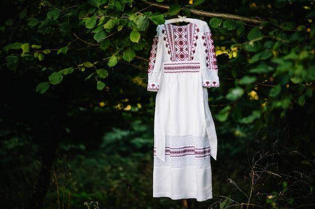 Белое, красное свадебное платье для невесты на вешалке, висящей на ветке дерева в саду на открытом воздухе.