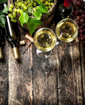 White and red wine with branches of grapes on wooden table.