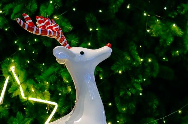 赤いアントラーと白いトナカイは、ライトでクリスマスツリーの装飾の前に立っています