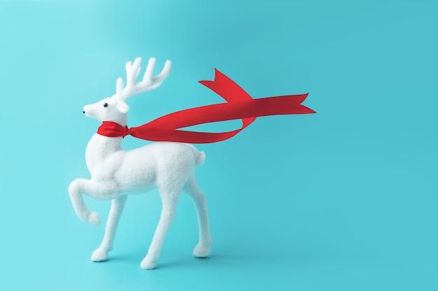 Белый олень с красной лентой