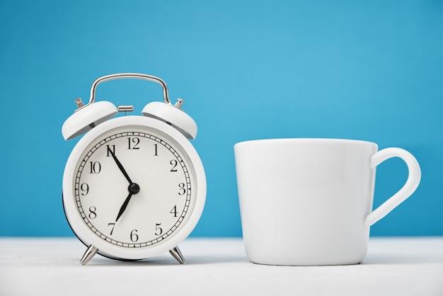 흰색 복고풍 알람 시계와 파란색 배경에 컵. 아침 시간 개념