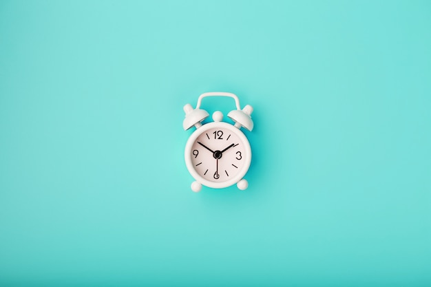 White retro alarm clock on blue background. concept of time with free space for text.
