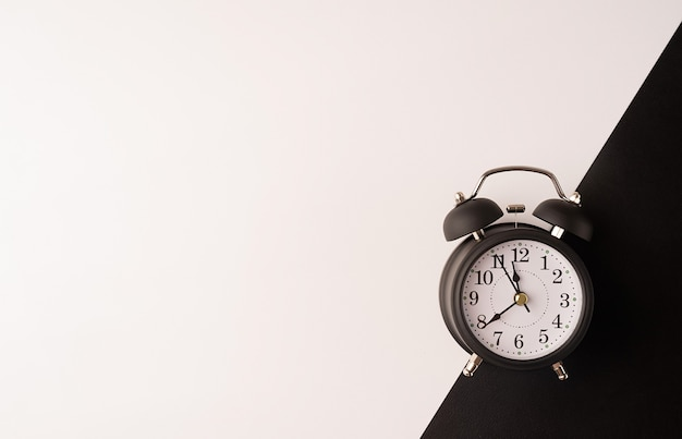 White retro alarm clock isolated on double white and black background with copy space