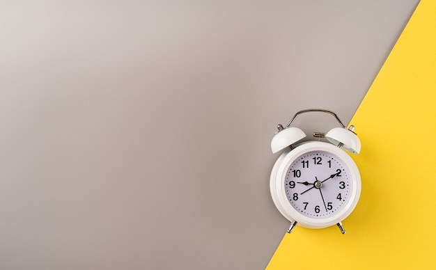 White retro alarm clock isolated on double yellow and gray background with copy space