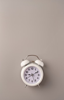 White retro alarm clock isolated on gray background with copy space