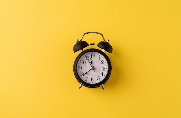 White retro alarm clock isolated on yellow background with copy space