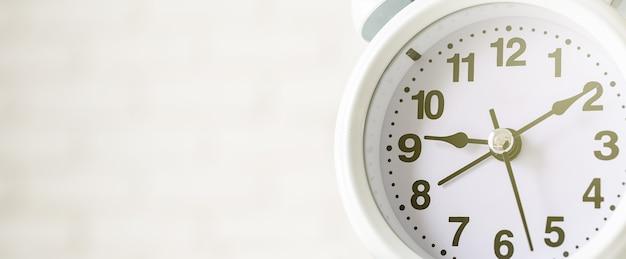 White retro alarm clock on white brick wall background