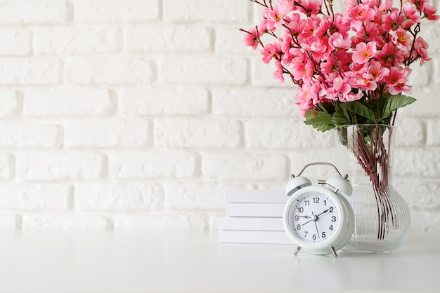 White retro alarm clock on white brick wall with books and flowers with copy space