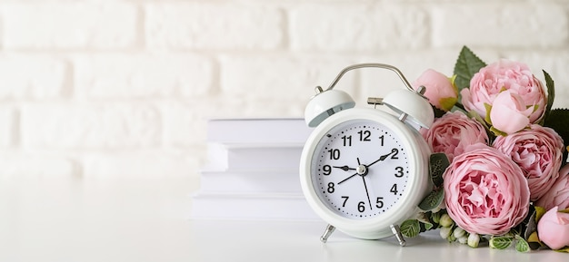 White retro alarm clock on white brick wall with books and peonies with copy space