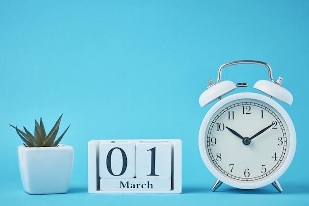 青い背景に鐘と木製のカレンダーブロックと白いレトロな目覚まし時計