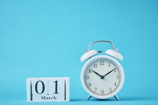 鐘と木製のカレンダーブロックと白いレトロな目覚まし時計